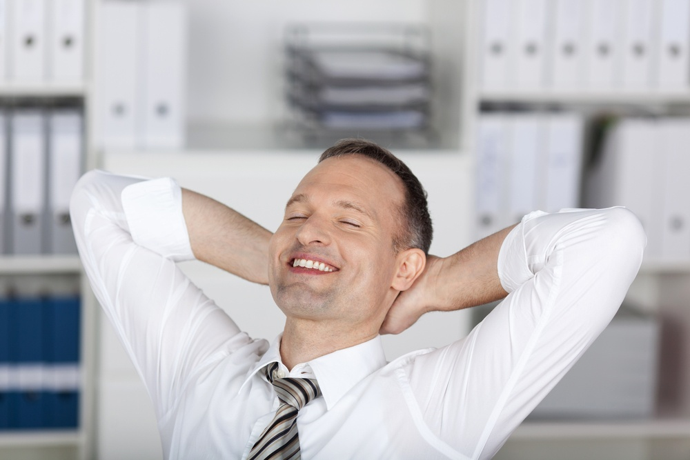 Smiling businessman sitting and relaxing at the office.jpeg
